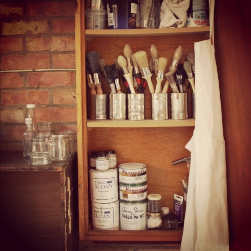 From bottom: A variety of Annie Sloan Chalk Paints and waxes and various upholstery tools; My wide selection of brushes {but none so useful as my trusty all-rounder, the Create Vintage paintbrush}; various pots, cloths and scraps of sandpaper
